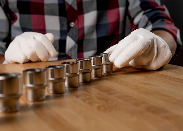 Main masculine et rangée de lignes de douilles hexagonales en acier métallique ou de têtes métalliques hexagonales sur une table en bois. outil en métal de réparation de voiture et de maison, gros plan.