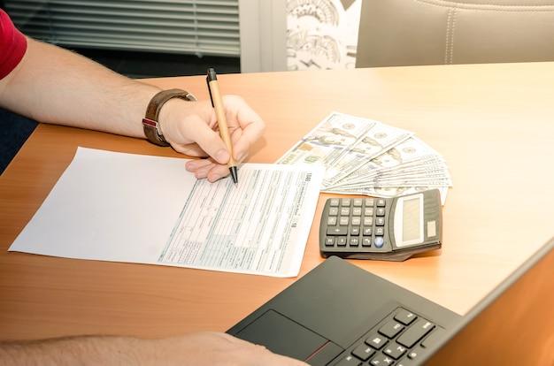 La main masculine remplit 1040 formulaires fiscaux au bureau