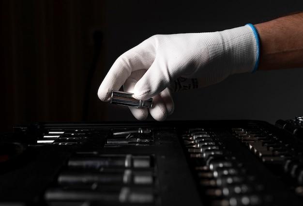 Main masculine se bouchent dans un gant blanc sur une boîte à outils ouverte avec des outils métalliques pour la réparation de voitures et de maisons, tête.
