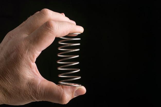 La main masculine serre un ressort métallique sur fond noir