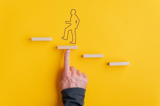 Main masculine soutenant une étape dans l'escalier métaphorique pour un homme qui se profile pour marcher vers le haut dans une image conceptuelle.