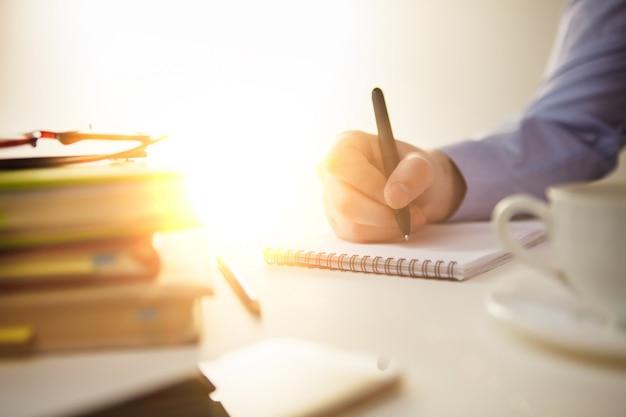 Main masculine avec un stylo et une tasse