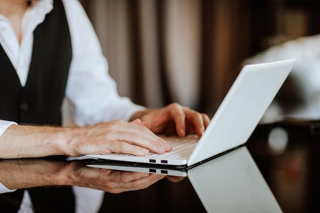 Main masculine tapant sur un ordinateur portable blanc placé sur un concept d'entreprise de table en verre foncé