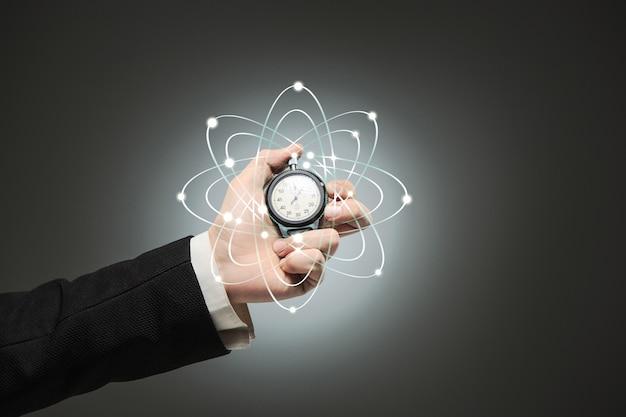 La main masculine tenant un chronomètre sur un fond blanc