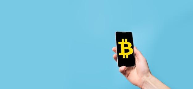 Main masculine tenant une icône de bitcoin sur fond bleu. bitcoin cryptocurrency digital bit coin btc currency technology business internet concept.