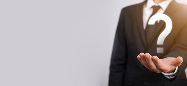 Main masculine tenant l'icône de point d'interrogation sur fond néon rouge, bleu, violet. bannière avec espace de copie. place pour le texte.