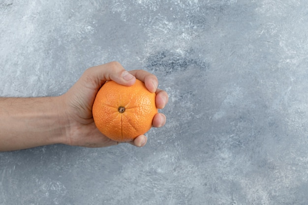 Main masculine tenant une seule orange sur une table en marbre.