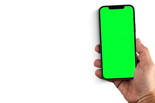 Main masculine tenant un smartphone avec un écran vert. clé chroma. isolé sur fond blanc.