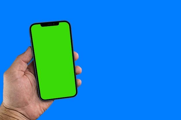 Main masculine tenant un smartphone avec un écran vert. clé chroma. isolé sur fond bleu.