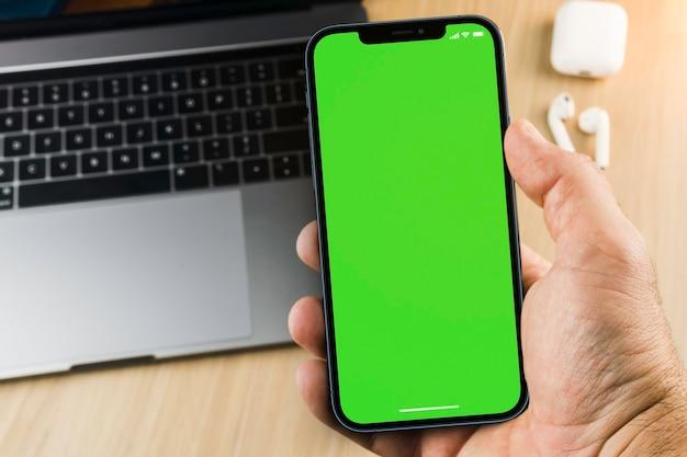 Main masculine tenant un smartphone avec un écran vert sur fond en bois avec un ordinateur. vue de dessus. clé chroma.