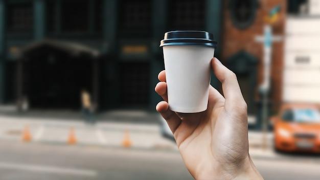 Main masculine tenant une tasse de café en papier blanc avec une casquette noire sur la maquette d'arrière-plan flou de la ville