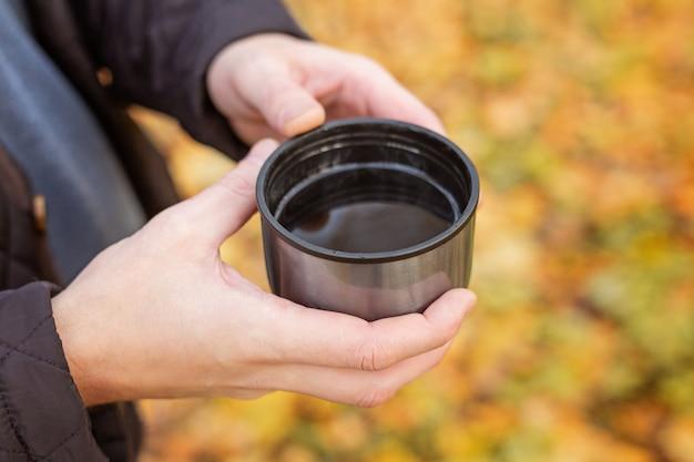 Main masculine tenant une tasse thermos avec du thé noir chaud dans la forêt d'automne - image