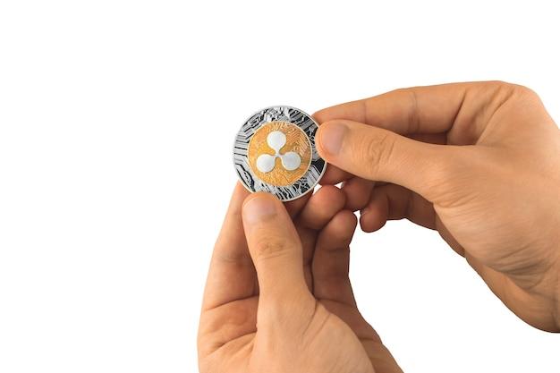 La main masculine tient un isolat de crypto-monnaie de pièce d'ondulation sur la photo de fond blanc