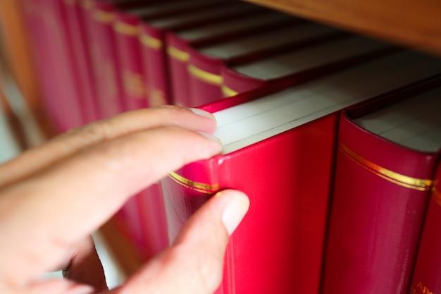 Une main masculine tire le livre rouge sur une étagère de la bibliothèque.