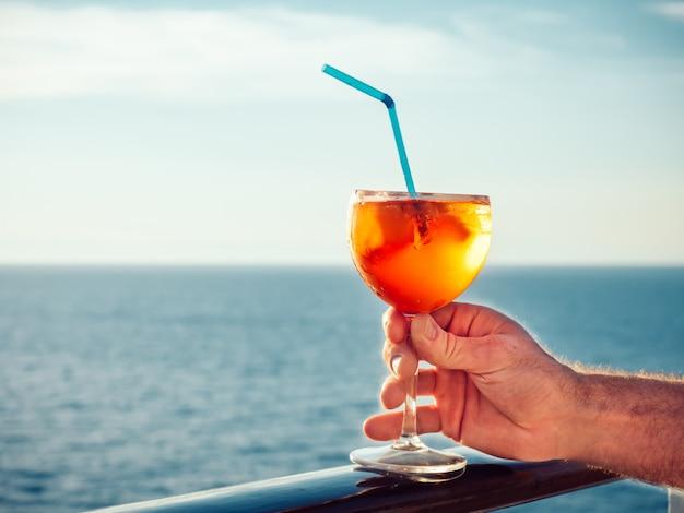 Main masculine avec un verre de beau cocktail rose