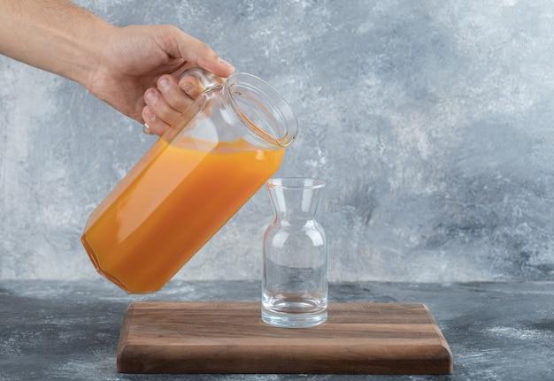 Main masculine versant du jus d'orange dans le verre.