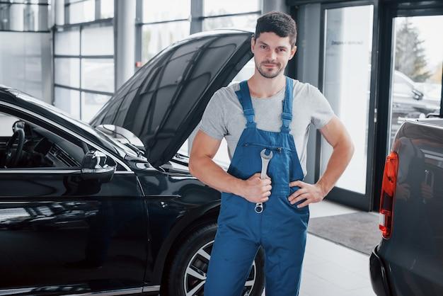 La main d'un mécanicien automobile avec une clé dans une zone mixte près de la voiture dans l'atelier.