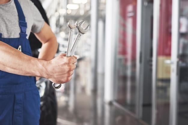 Main de mécanicien automobile avec clé. garage de réparation automobile.