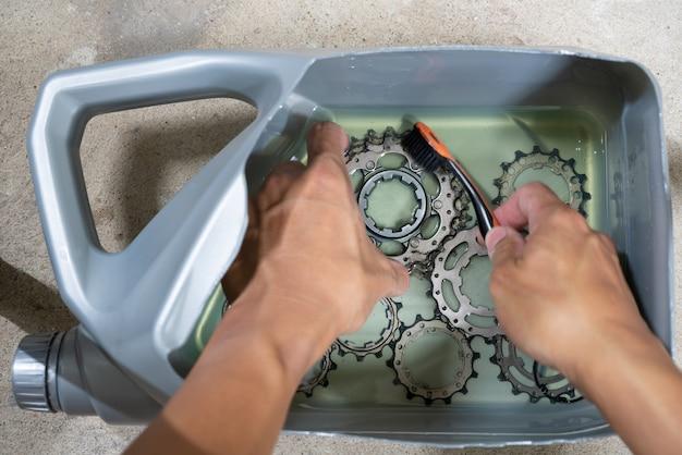 Main d'un mécanicien en train de nettoyer une cassette de vélo avec du carburant diesel.