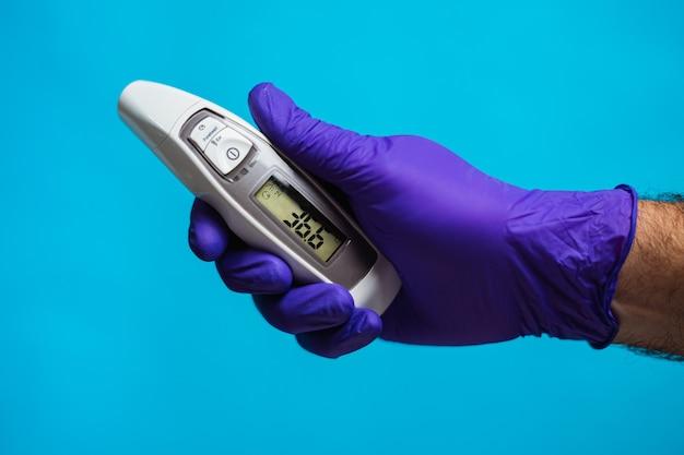 Une main de médecin tenant un thermomètre sur fond bleu protection contre les coronavirus