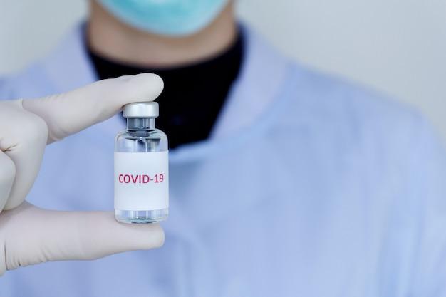 Main de médecin tenant le vaccin bouteille covid-19, concept de traitement médicamenteux.