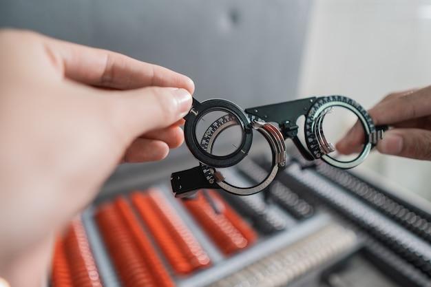 La main d'un médecin tient la monture de lentille expérimentale dans une pièce d'une clinique ophtalmologique avec l'arrière-plan de la boîte de monture de lunettes