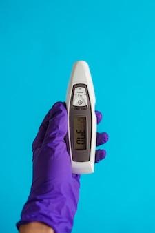 Une main de médecins portant un gant violet tenant un thermomètre sur fond bleu