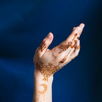 Main avec mehndi près du textile bleu