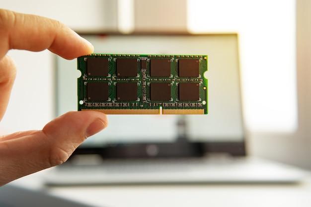 Main avec mémoire sur une carte mère d'ordinateur. ram en main sur le fond de l'ordinateur portable.