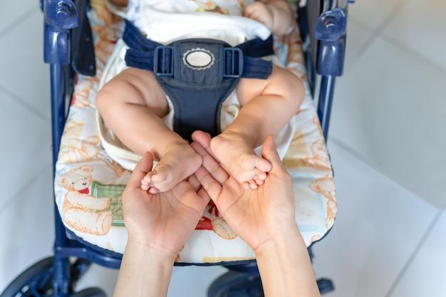 Main de la mère tenant les pieds de bébé pendant son sommeil dans une poussette.
