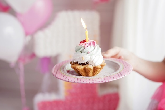 Main de mère tenant le premier gâteau d'anniversaire avec une bougie