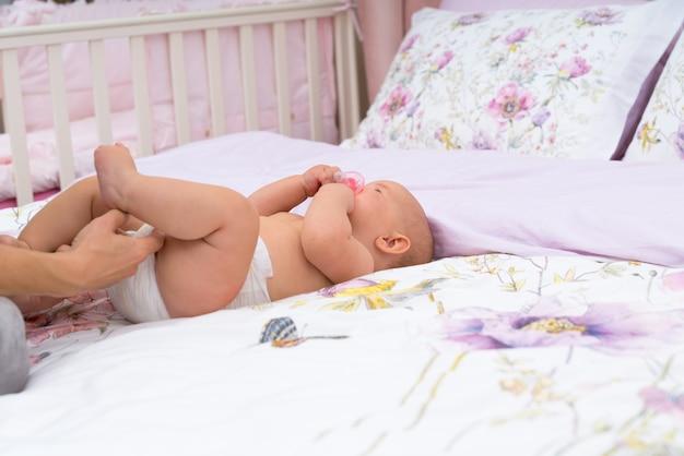 Main de mères vérifiant sa couche de bébé, alors qu'elle repose sur le dos sur les draps sur le lit, vue en gros plan avec copie espace