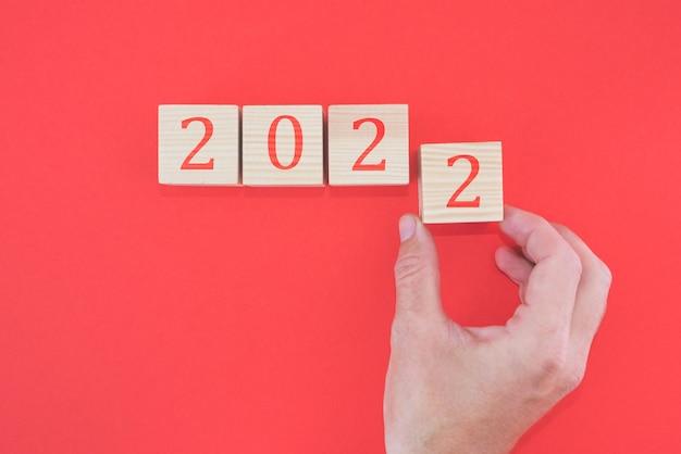 La main met le bloc à partir de 2022 sur fond rouge. notion de nouvel an. 2022 sur des cubes de bois