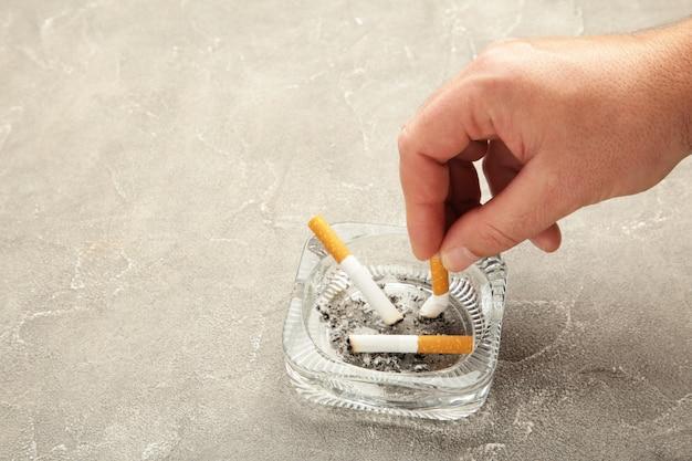Une main met une cigarette dans un cendrier sur fond de béton gris. vue de dessus.
