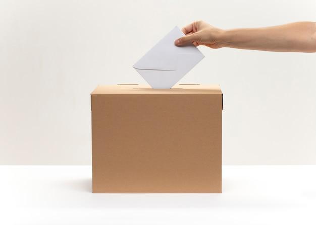 Une main met une enveloppe blanche dans la boîte de vote