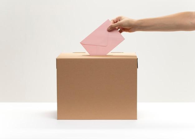 Une main met une enveloppe rose dans la boîte de vote