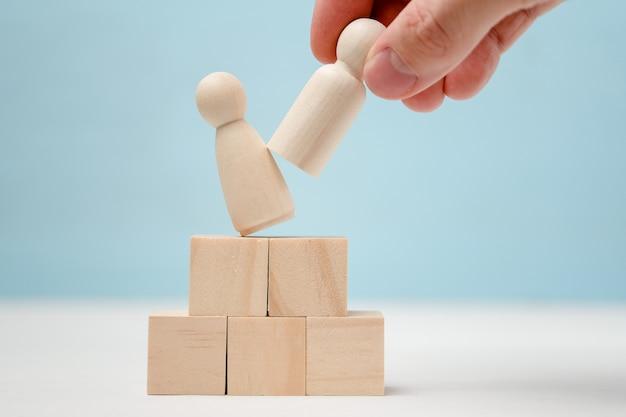 Main met une figurine en bois sur le podium, déplaçant celle qui se tient là.