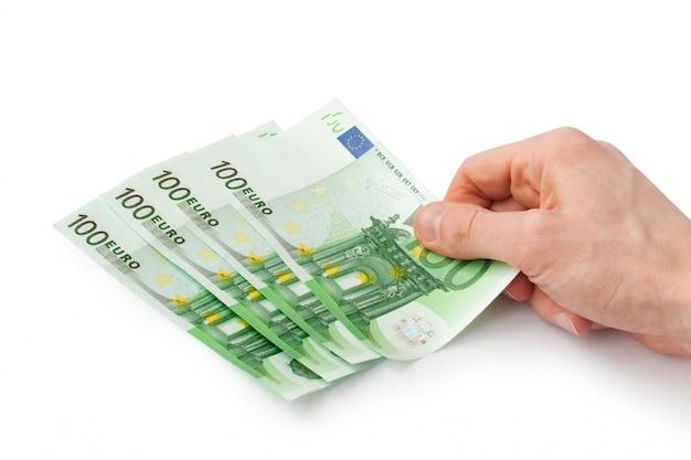 Main met quelques billets en euros isolés sur blanc