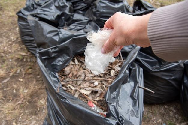 Une main met un sac en plastique blanc dans un sac poubelle.