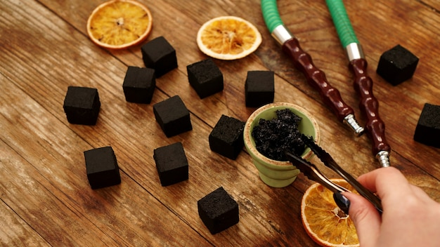 La main met le tabac dans le bol pour le narguilé sur table en bois avec du charbon et des tranches d'orange séchées