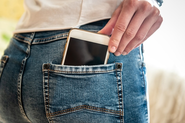 La main met le téléphone dans la poche du jean.