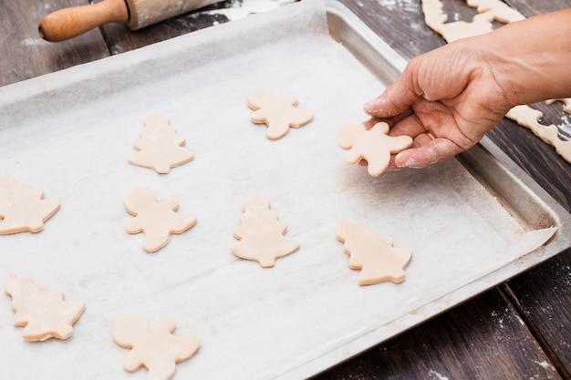 Main mettant des biscuits en forme de noël sur une plaque à pâtisserie