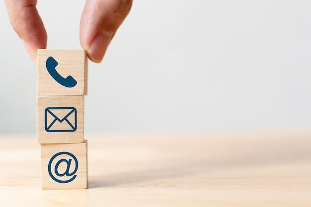 Main mettant en bois symbole cube cube téléphone, email, adresse