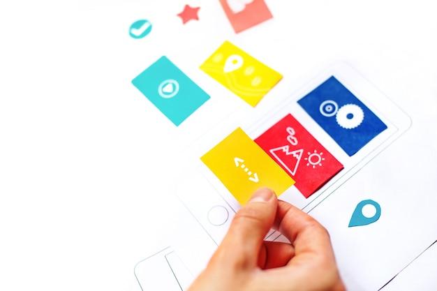 Main mettant des cartes en papier sur un téléphone dessiné à la main