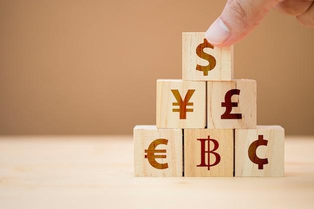 Main mettant un cube en bois de signe dollar américain à yuan yen euro et signe de livre sterling.