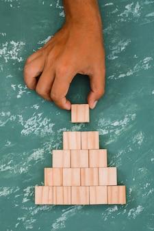 Main mettant et empilant le cube en bois.