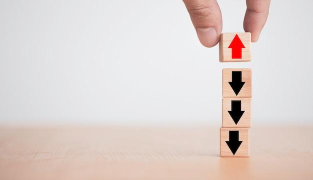 Main mettant la flèche rouge sur le bloc de cube en bois sur la flèche noire dans la direction opposée.