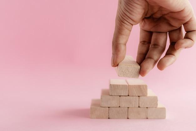 Main mettant le jouet en bois sur le mur rose