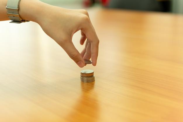 Main mettant la pièce sur la pile de pièces avec épargne, concept de finance.