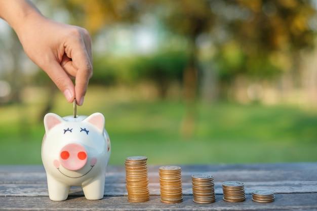 Main mettant la pièce sur la tirelire. retraite, finance et économie d'argent pour le futur